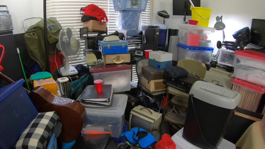 Hoarder home room packed full of household items, vintage electronics, business equipment and miscellaneous junk. | Shutterstock HD Video #1025933048
