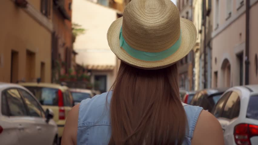Back view of young woman in hat walking down small old street in Rome, Italy. Happy female traveler in Trastevere district. Slow motion of girl looking around outside in european city | Shutterstock HD Video #1025940038