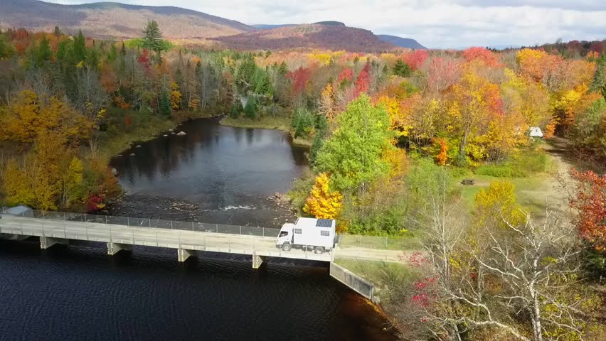 A camping truck drives across a bridge from a campground in a colorful autumn forest | Shutterstock HD Video #1025940188
