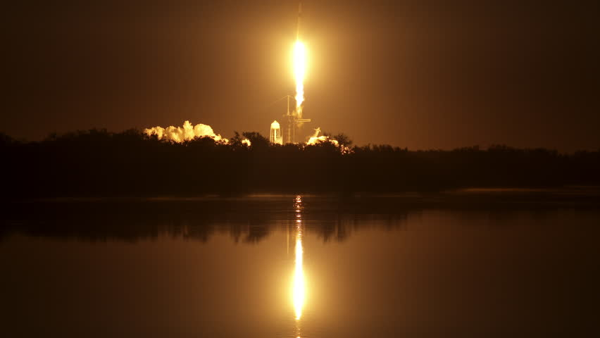 Beautiful reflection on water as a NASA space rocket flies into the night sky from the launch pad at night with flames and fire from the powerful engines. 4K. With sound and slow motion. | Shutterstock HD Video #1025952188