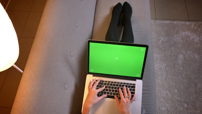 Closeup shoot of young female blogger typing on the laptop with green screen. Girls legs in cute socks on the cozy sofa | Shutterstock HD Video #1025959538