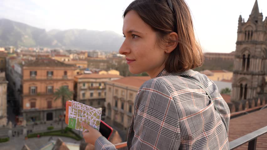 Happy tourist girl watching panorama of Palermo, Sicily, holding map of the city. Travel around Italy | Shutterstock HD Video #1025974748