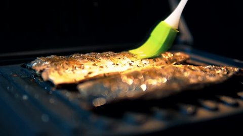 Chief Lubricates The Pieces Of Fish On Grill.Fish Fried On A Grill.Fish Lying On Grill Barbecue Are Sprinkled With Seasoning And Salt For Smoking. Raw Scomber With Spices.Stuffed Fish On Grill.