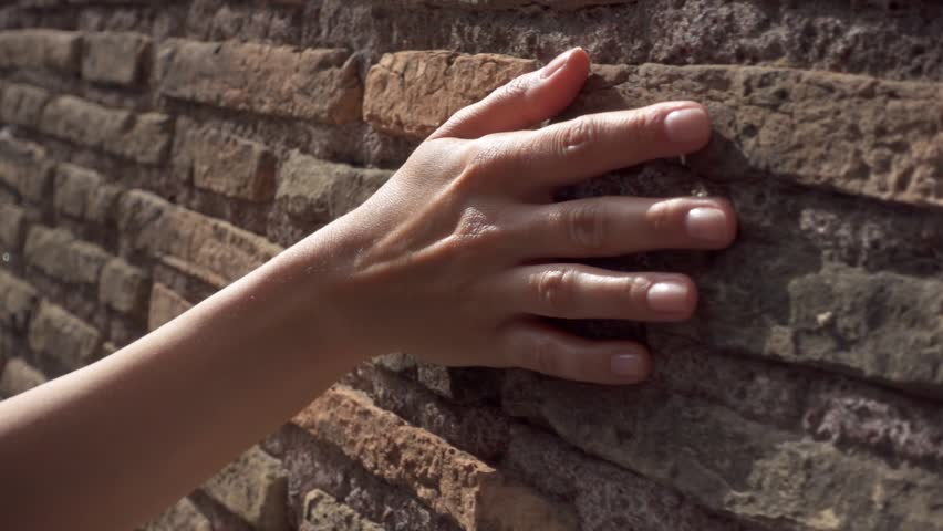 Woman sliding hand against old ancient red brick wall in slow motion. Female hand touching hard rough surface of stone bridge | Shutterstock HD Video #1026073508