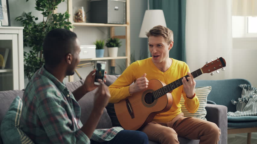 African American young man is holding modern smartphone and making video of his Caucasian friend playing the guitar and singing at home. Fun and gadgets concept. #1026193748