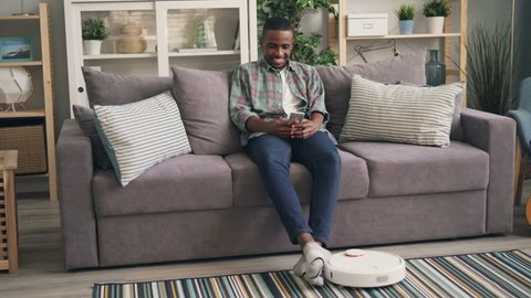 African American guy is using smartphone browsing enjoying modern technology while robotic vacuum cleaner is vacuuming carpet and floor in room at home.
