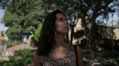 Diverse Young Woman Walks Through Park with Dappled Light - Mid Close Up from Front - Cinematic Slow Motion