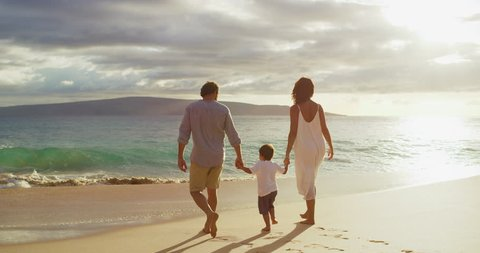 Happy mom and dad with small toddler son walking on the beach at sunset, island family vacation