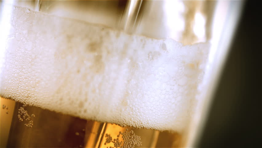 Beer is pouring into angled glass. IPA on tap. Cold Light Beer in a glass with water drops. Craft Beer forming waves close up. Freshness and froth. Bar background. Microbrewery craft beer. | Shutterstock HD Video #1026296498