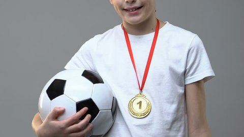 Boy with soccer ball and first place medal standing against grey background