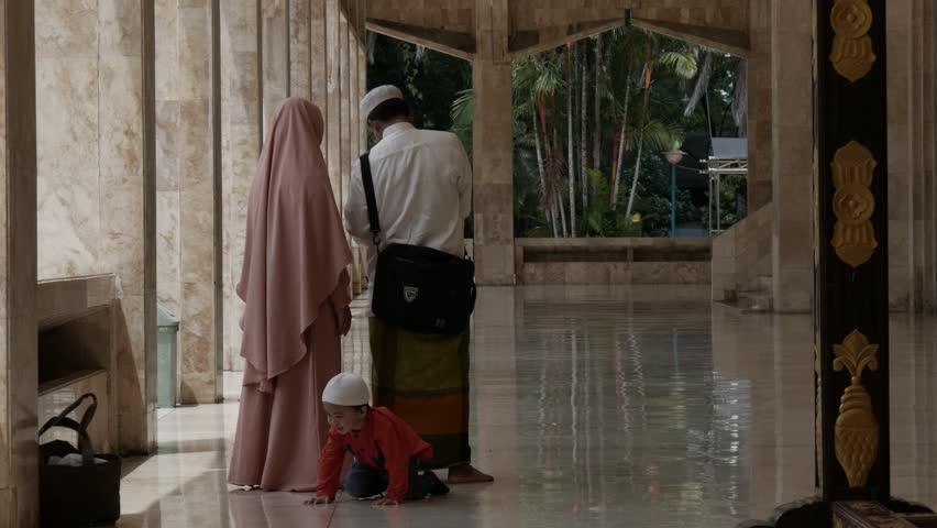 BANJARMASIN, SOUTH KALIMANTAN/BORNEO, INDONESIA - 03/24/2019: Indonesian Muslim family walking around in the terrace of Sabilal Muhtadin Mosque. Shot in 4K UHD. #1026339788