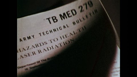 1970s: UNITED STATES: TB MED 279 guidelines. Man knocks on door. Man enters room. Personnel work with lasers. Reflection on lens