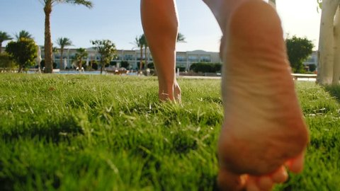 Close up of young girl legs running barefoot on the green grass. Slow motion shot of bare feet of young girl walking on fresh grass from hotel room to swimming pool.