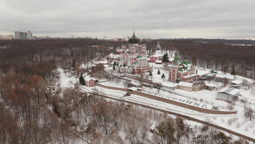 Flying over frozen river and snowy landscape of Theophania park and large eastern orthodox cathedral in the Kievan neighborhood - flying forward | Shutterstock HD Video #1026361568