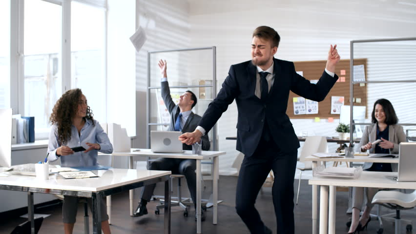 Businessman speaking on phone and then shouting good news to team and start dancing with excitement in center of office while colleagues smiling and taking pictures of him with smartphones   Shutterstock HD Video #1026395708