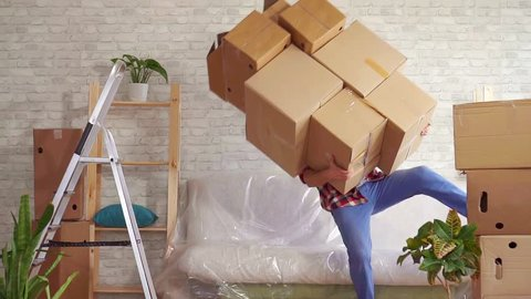 Man with heavy boxes in his hands loses his balance and falls on the sofa slow mo
