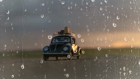 NITRA, SLOVAKIA - JUNE 28 2018: Volkswagen Beetle with suitcases on the roof. Summer rain and Volkswagen Beetle. Classic car VW Beetle by rain.