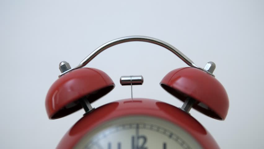 A close-up of a bell from a vintage red alarm clock that triggers the alarm.