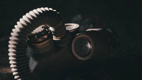 The gas mask lies on the ground. The camera gradually focuses.