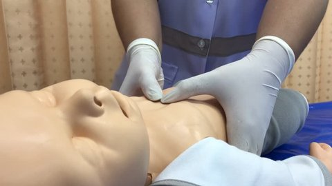 CPR training medical procedure demonstrating chest compressions on CPR doll.