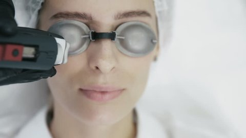 Close up cosmetologist hands with special equipment does laser procedure for removal of blood vessels on girl's face. Beautician makes laser treatment on young woman face. Concept medical clinic