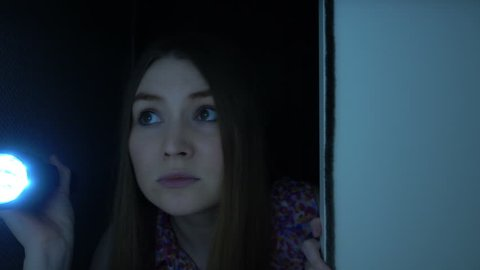 POV of Attractive blond-haired woman holding flashlight and opening a door, checking a room in the darkness. Nightmare of young woman that feels fear and scare.