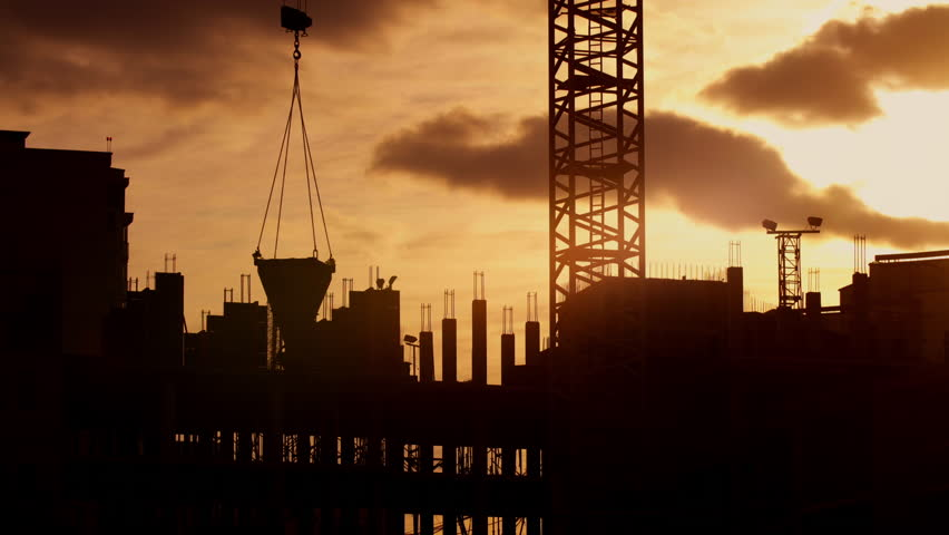 Silhouette of tower crane working on construction site elevate cement mixer, constructors working on residential building sunny evening, golden hour, warm cloudy sky