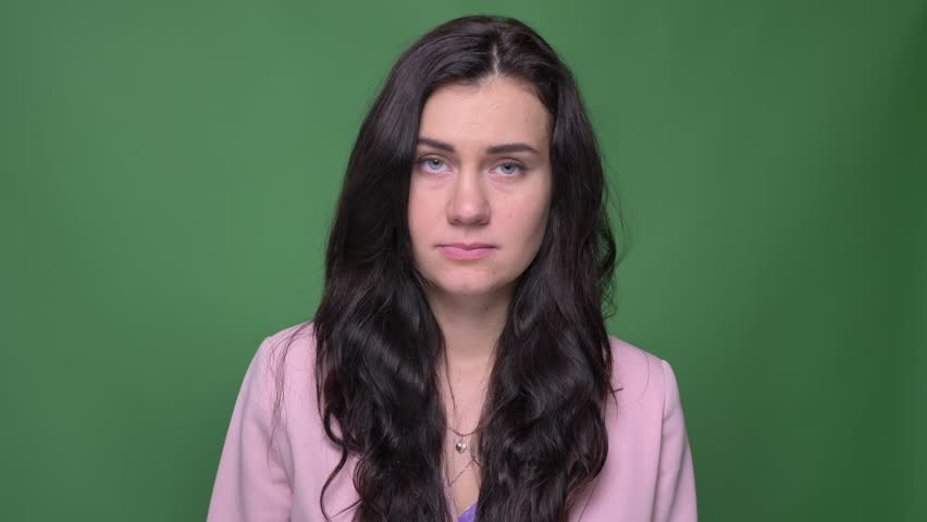 Portrait of brunette businesswoman in pink jacket watches with great pain and sorrow into camera on green background | Shutterstock HD Video #1026580148