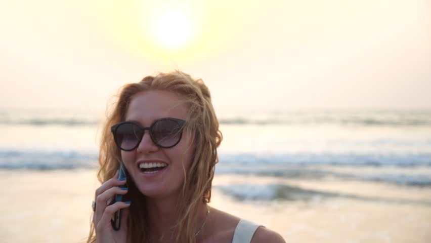Happy cute young blonde girl in sunglasses smiling and talking on the phone against the sea. A joyful beautiful woman in spectacles calls on her smartphone and laughs.