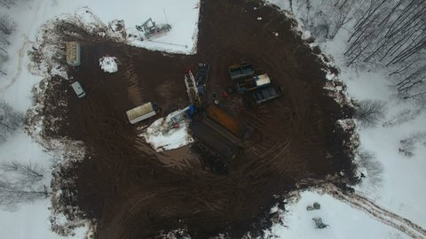 Drilling a deep well with a drilling rig in an oil and gas field in winter forest. Field is located in Kamchatka, Tundra, Yamal, North, West, Siberia, fog, aerial, snowfall, flakes, snowstorm, up view