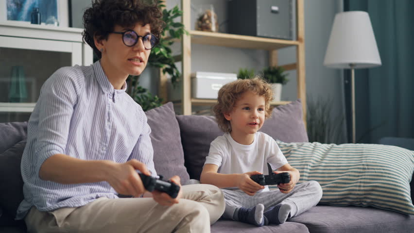 Happy family mother and son are playing video games in apartment having fun together, boy is jumping expressing positive emotions. Modern children and devices concept. | Shutterstock HD Video #1026706598