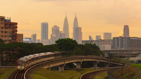 Time lapse of a busy train tracks with train MRT LRT moving with Kuala Lumpur city skyline silhouette from afar in the background with golden sky in Federal Territory, Malaysia.