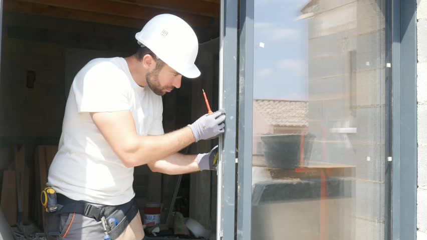 Handsome young man installing bay window in a new house construction site  | Shutterstock HD Video #1026787448