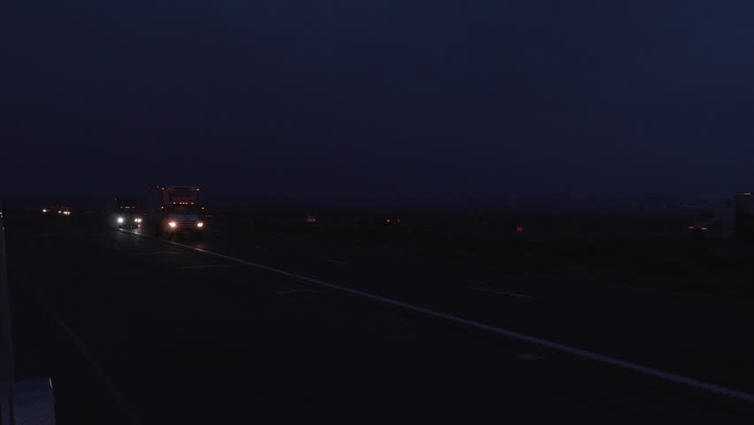 This is a shot of a tractor trailer driving into the sunset on a desert road. Shot on a GH5 | Shutterstock HD Video #1026794048