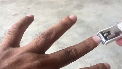 Close up of finger nails cutting using nail clipper to maintain and good personal hygiene.