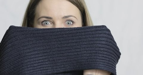 Close-up of a woman slowly lowering her scarf and peeking out, playing peek-boo
