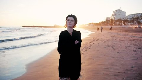 Happy delighted girl walks on beach towards camera in sunset light. Beautiful stylish female feeling inspired, moody smiling enjoying holidays, vacation in lovely sea town slow motion
