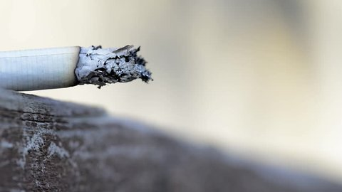 Someone forget a burning cigarette on pine wood board, conceptual footage of danger, fire.