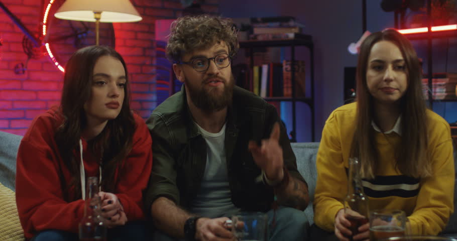 Caucasian young stylish people sitting on the sofa at home at night talking, drinking beer and watching TV. | Shutterstock HD Video #1026957938