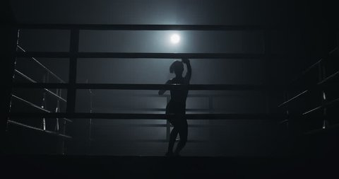 Female boxer training in the dark ring. Slow motion. Silhouette. Boxing concept