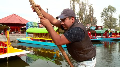 "October 21st, 2015. Xochimilco, Mexico City. Mexico. A man rows a traditional boat called ""trajinera"" through Xochimilco channels."