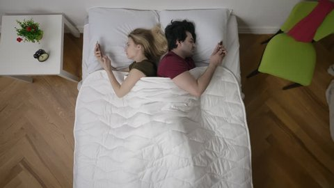 Young couple in bed using phone lying backs to each other. Relationship difficulties