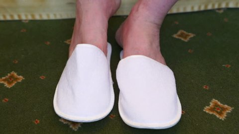 Man in hotel room slippers sitting on bed. White closed toe disposable slippers.