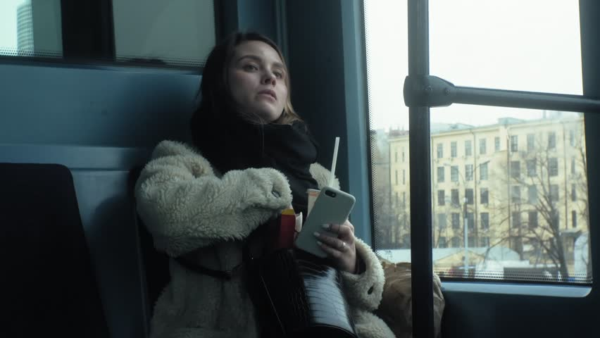 Beautiful young brunette woman riding in the subway car, eating fast food, french fries, drinking a drink, using the phone, looking out the window | Shutterstock HD Video #1027156178