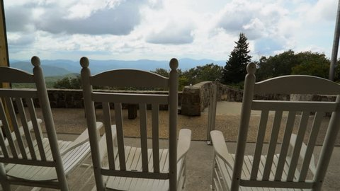 A peaceful, serene, scene of rustic, white rocking chairs on a deck overlooking the Appalachian mountain peaks at Brasstown Bald, Georgia.