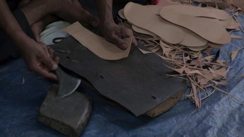 Shoe maker using traditional hand tools, sharpening it on stone, to cut leather soles for footwear in precise shape while seated on the floor and working at a shop in Anjuna flea market in Goa, India