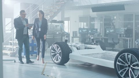 Female and Male Engineer Walk in a High Tech Development Facility Holding a Tablet Computer. They Pass an Electric Car Chassis Prototype with Batteries and Wheels.