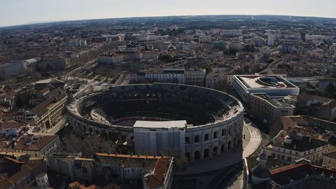Circular aerial shot around the Roman amphitheatre Arena of Nîmes elliptical building