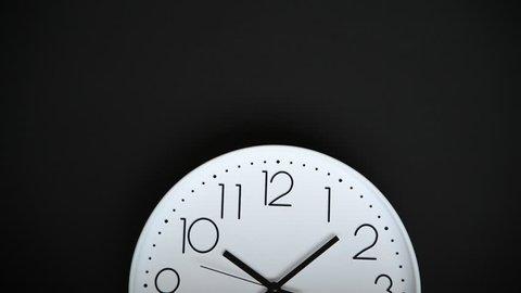 Closeup single white clock hanging on black background