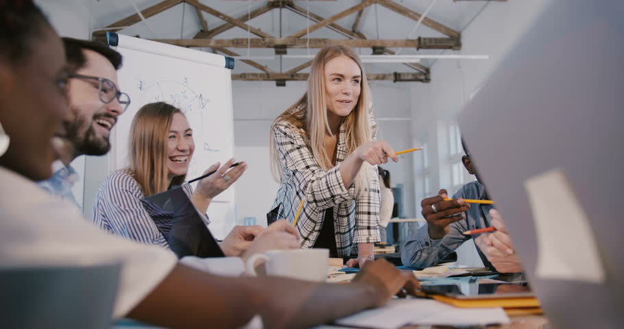 Young successful attractive female team leader working together with creative multiethnic employees at office meeting. | Shutterstock HD Video #1027342448